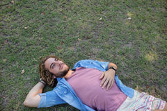 Fundersam man som ligger på gräs med handen bak huvudet Royaltyfri Fotografi