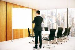 Fundersam man som ser whiteboard Fotografering för Bildbyråer
