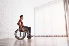 Fundersam man som sitter i rullstol nära fönster arkivbild