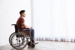 Fundersam man som sitter i rullstol nära fönster royaltyfri foto