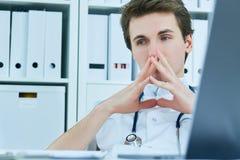 Fundersam manlig doktor som ser bort, medan sitta på stol i medicinskt kontor royaltyfria bilder