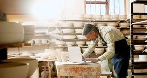 Fundersam manlig keramiker som arbetar på bärbara datorn 4k arkivfilmer