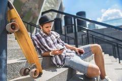 Fundersam manlig skateboradåkare som lyssnar till musikformhörlurar Royaltyfri Fotografi
