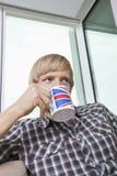 Fundersam mitt--vuxen människa man som hemma dricker kaffe i vardagsrum Arkivbilder
