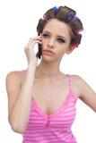 Fundersam modell i hårrullar på telefonen Royaltyfri Foto