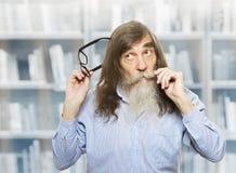 Fundersam pensionär med exponeringsglas som tänker den inspirerade eftertänksamma gamala mannen Arkivbild