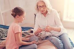 Fundersam pensionerad kvinna som ger hennes kunskap av handarbete arkivbild