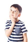 Fundersam pojke med fingret på hakan Royaltyfri Bild