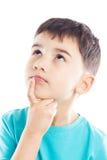Fundersam pojke med fingret på hakan Arkivfoton