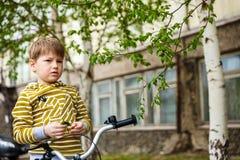 Fundersam pojke på en cykelritt arkivfoton