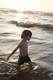 Fundersam pojke som djupt går knäet i havet Arkivfoto