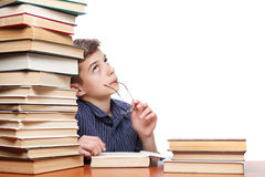 Fundersam pojke som ser upp och drömmer av en bokbunt på vit bakgrund arkivbilder