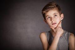 Fundersam pojke som ser upp på grå färger med kopieringsutrymme Royaltyfri Foto