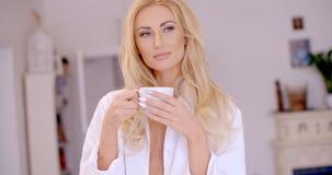 Fundersam sexig blond kvinna med en kopp kaffe Arkivfoto