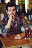 Fundersam skäggig man som bär tillfällig kläder som sitter i en modern bar arkivbilder