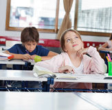 Fundersam skolflicka som ser upp, medan genom att använda Royaltyfri Fotografi