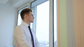 Fundersam stilig chef som ser in i avståndet från fönstret stock video