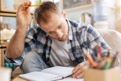 Fundersam stilig man som skrapar hans huvud med en blyertspenna Fotografering för Bildbyråer