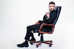 Fundersam stilig stol för affärsman som i regeringsställning pekar på dig royaltyfria foton