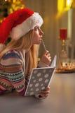 Fundersam tonårs- flicka i den santa hatten med dagboken i kök Arkivbilder