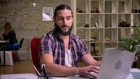 Fundersam tvivla blick av denuppsökte caucasian mannen som ser kusligt på skärmen av hans bärbar dator och sitter på stock video
