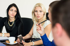 Fundersam ung affärskvinna med en grupp av affärsfolk Fotografering för Bildbyråer