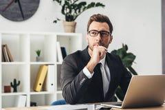 fundersam ung affärsman på arbetsplatsarbete arkivbild