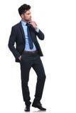 Fundersam ung affärsman som ser till hans sida Fotografering för Bildbyråer