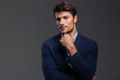 Fundersam ung brunettman i blått omslag som tänker om något royaltyfria foton
