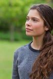 Fundersam ung flicka som ser in mot sidan Fotografering för Bildbyråer