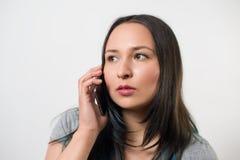 Fundersam ung flicka som talar på telefonen och bort ser p? ljus bakgrund arkivfoto