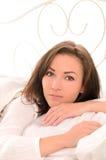 Fundersam ung härlig kvinna på säng Arkivbild