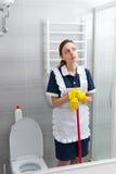 Fundersam ung hembiträde som tar ett avbrott från hennes arbete Arkivbild