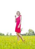 Fundersam ung kvinna i smörblommafält Arkivbilder