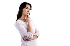 Fundersam ung kvinna med handen på hakan Royaltyfri Fotografi