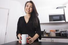 Fundersam ung kvinna som har kaffe i kök arkivbild