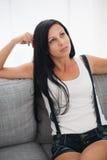 Fundersam ung kvinna som sitter på sofaen Royaltyfria Bilder