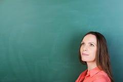 Fundersam ung lärare på svart tavla Royaltyfria Bilder