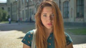 Fundersam ung ljust rödbrun kvinna som ser kameran och anseende på gatan, byggnad i bakgrund, eftertänksamt och bekymrat stock video