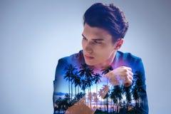 Fundersam ung man som drömmer mot tropisk bakgrund arkivbild