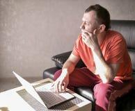Fundersam ung man som sitter nära bärbara datorn i hennes vardagsrum, Copyspace royaltyfria bilder