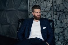 Fundersam ung modern man som sitter på fåtöljen royaltyfri foto