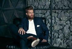 Fundersam ung modern man som sitter på hans arbetsplats royaltyfria bilder