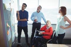 Fundersamma affärsentreprenörer som ser whiteboard royaltyfria foton
