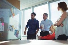 Fundersamma affärskollegor som i regeringsställning ser whiteboard arkivbild