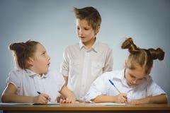 Fundersamma flickor och liten skolpojke på grå bakgrund skola för copyspace för begrepp för svarta böcker för bakgrund royaltyfri fotografi