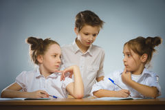 Fundersamma flickor och liten skolpojke på grå bakgrund skola för copyspace för begrepp för svarta böcker för bakgrund royaltyfri bild