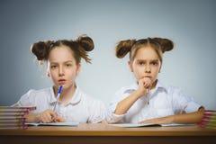 Fundersamma flickor som sitter på skrivbordet på grå bakgrund skola för copyspace för begrepp för svarta böcker för bakgrund royaltyfri fotografi