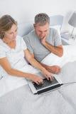 Fundersamma par genom att använda deras bärbar dator tillsammans i säng Arkivfoton