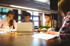 Fundersamma studenter som tillsammans arbetar på skrivbordet genom att använda bärbara datorn Arkivfoton